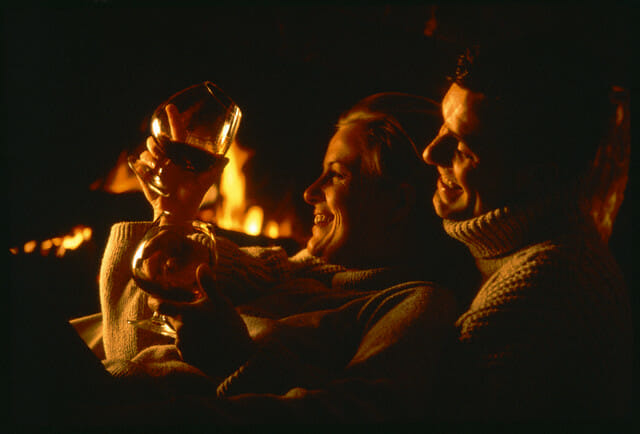 Mature Couple Holding Cognac Glasses and Embracing in Front of Open Fire