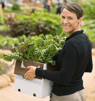 woman holding box of vegetables Discover: Community Farms - EAT LOVE SAVOR International luxury lifestyle magazine, bookazines & luxury community