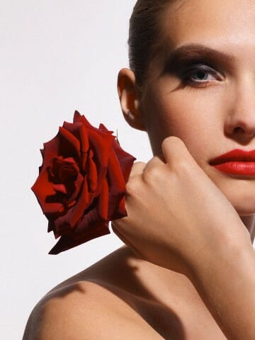 Young woman with a red rose --- Image by © Robert Freeman/Corbis