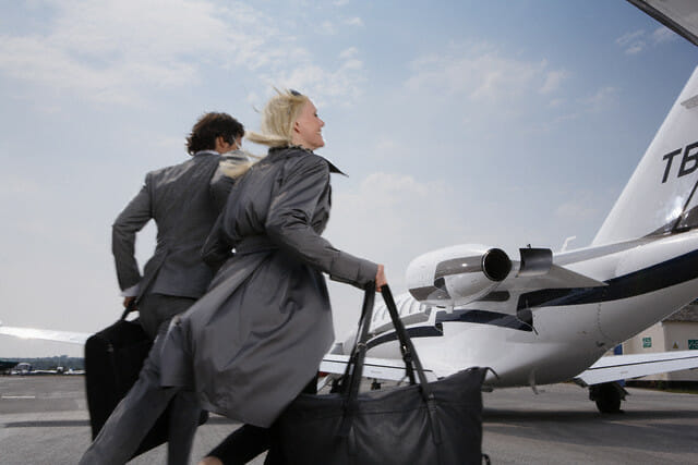 Couple Rushing to Their Private Jet --- Image by © Dirk Lindner/Corbis