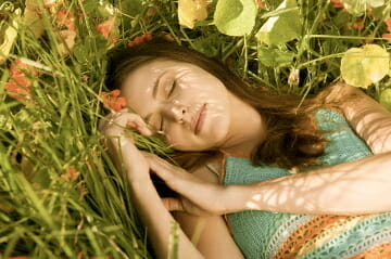 Woman napping in grass and flowers Discover: Summer Naps - EAT LOVE SAVOR International luxury lifestyle magazine, bookazines & luxury community