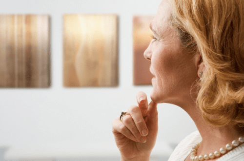 pensive woman looking at art Should I Collect Prints or Paintings? - EAT LOVE SAVOR International luxury lifestyle magazine and bookazines