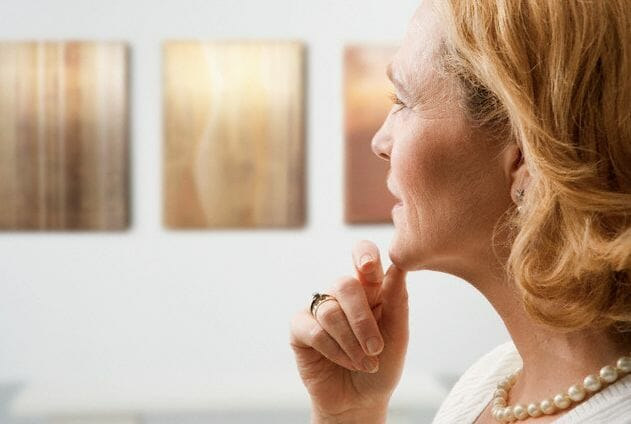 pensive woman looking at art Should I Collect Prints or Paintings? - EAT LOVE SAVOR International luxury lifestyle magazine, bookazines & luxury community