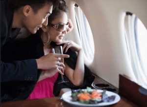 Couple with Wine Looking out Plane Window Get on the Fast Track to Luxury with Visa, Premium Access Program - EAT LOVE SAVOR International Luxury Lifestyle Magazine
