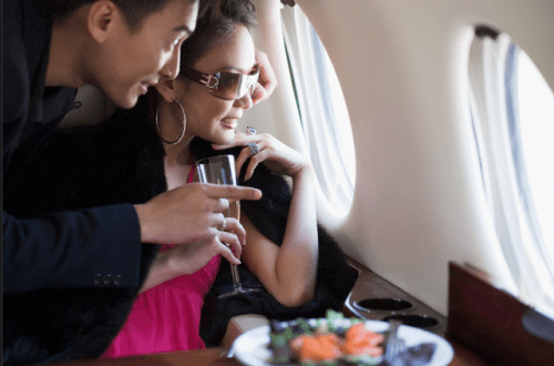 Couple with Wine Looking out Plane Window Get on the Fast Track to Luxury with Visa, Premium Access Program - EAT LOVE SAVOR International luxury lifestyle magazine and bookazines